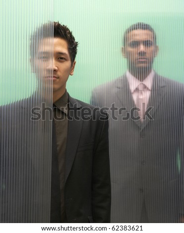 Businessmen obscured by glass walls