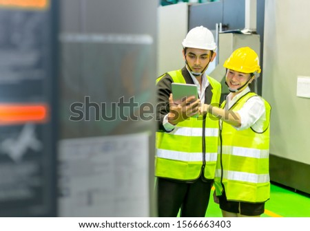 Businessmen or male engineers and female engineers are working in industrial plants that have machines and injection molds, with tablets used to control technology.