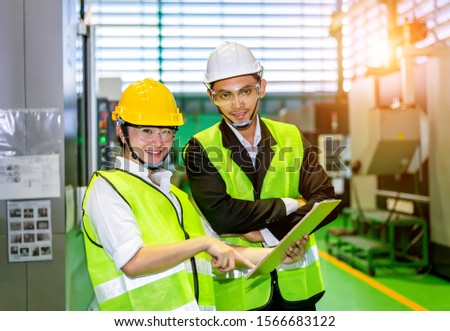 Businessmen or male engineers and female engineers are working in industrial plants that have machines and injection molds