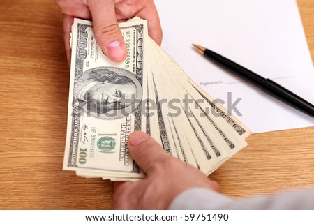 Businessmen passing money with contract on the background