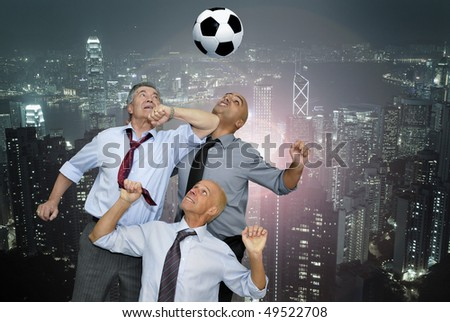 Businessmen playing  soccer outdoors