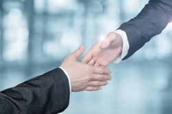 Businessmen reach out to each other to shake hands on a blurred background.