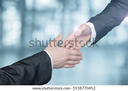 Businessmen reach out to each other to shake hands on a blurred background. Foto stock ©