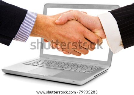 Businessmen shake hands from laptop computer