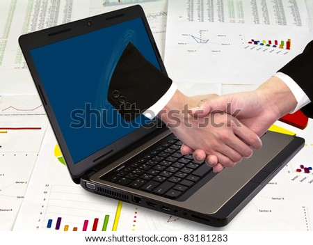 Businessmen shake hands from laptop on financial Graphs