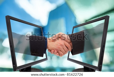 Businessmen shake hands from two lcd monitors
