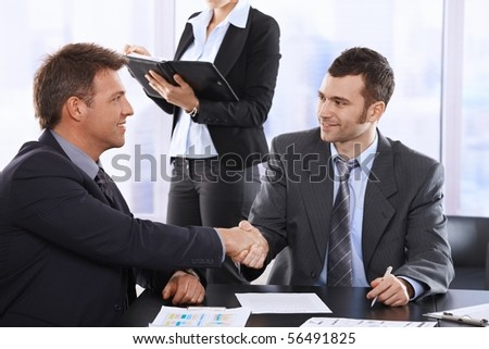 Businessmen shaking hands at meeting, sitting at table, assistant in background holding organiser.