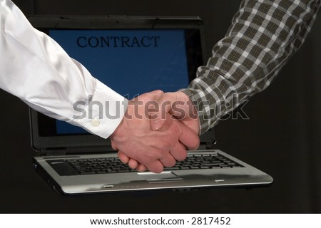 Businessmen shaking hands in front of a laptop