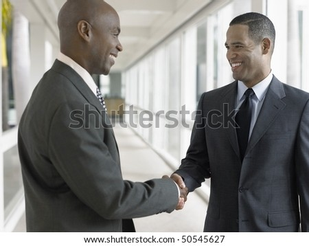 Businessmen shaking hands in hallway