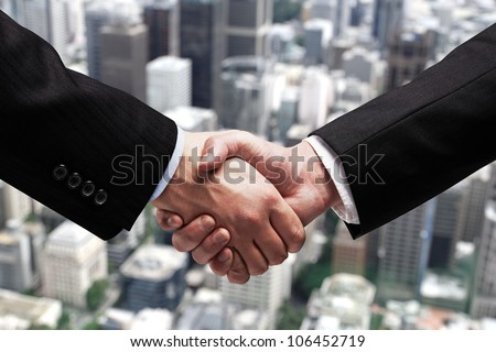 businessmen shaking hands on background of city