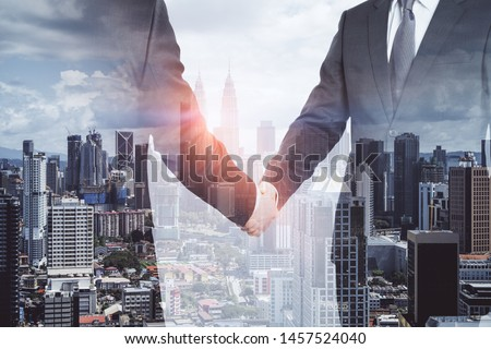 Businessmen shaking hands on blurry Kuala Lumpur city background. Teamwork and success concept. Multiexposure