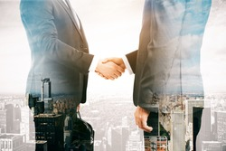 Businessmen shaking hands on city background. Double exposure. Partnership concept