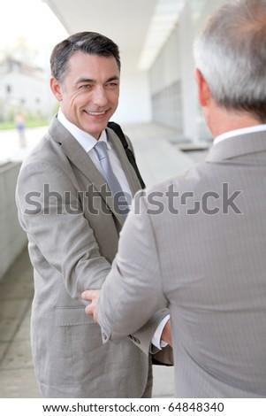 Businessmen shaking hands outside building