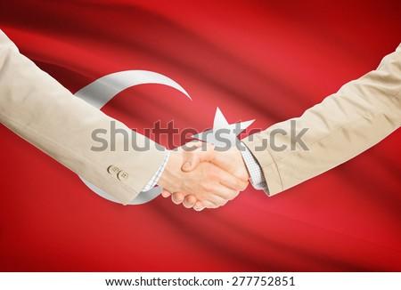 Businessmen shaking hands with flag on background - Turkey