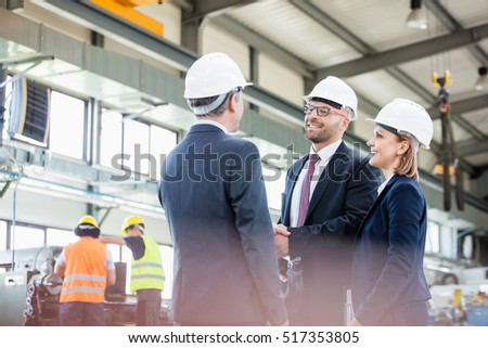 Businessmen shaking hands with workers working in background at metal industry #517353805