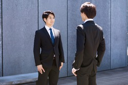 Businessmen standing facing each other