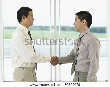 Businessmen standing, Shaking Hands in front of window, profile