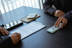 Businessmen submitting illegal money bribes in the form of cash For use in bribery of contracting his partners in illegal business practices, the idea of giving and receiving illegal bribes.