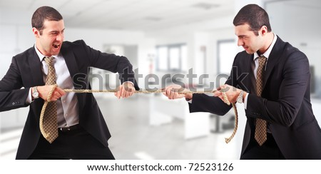 Businessmen twins pulling a rope in an office environment
