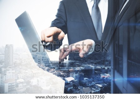Businessmen using laptop together on abstract city background. Teamwork and communication concept. Double exposure