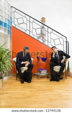 Businessmen waiting in office. Woman stepping up the staircase