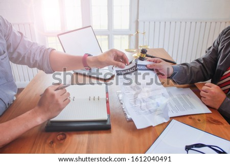 Businessmen who are stressed due to bankruptcy and are tearing the contract in front of the lawyer in the lawyer office. The concept of contract termination and unfair contract breaking