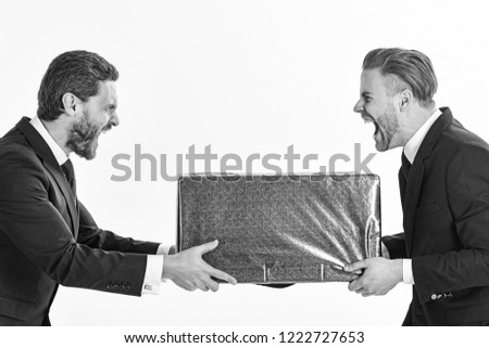 Businessmen with mad faces take away from each other blue package, isolated on white background. Two businessmen with aggressive expression pull box in opposite directions. Business rivalry concept. #1222727653