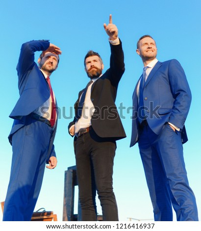 Businessmen with smiling faces in formal suits and ties on blue sky background. Executives take a walk outside. Business, confidence and teamwork concept. Company leaders show worksite and new goals