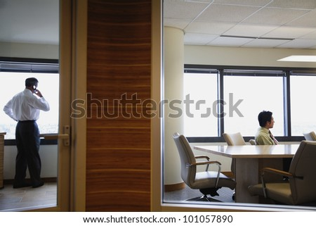Businessmen working in separate offices