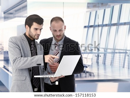 Businessmen working with laptop at office, discussing. Copyspace