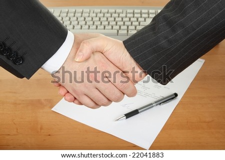 businessmens' handshake over contract and pen