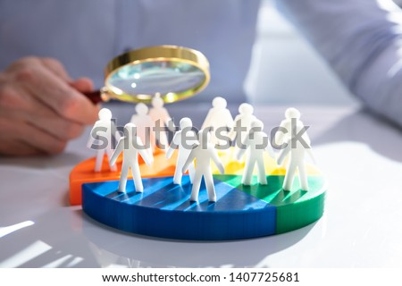 Businesspeople Analyzing Market Segment Using Magnifying Glass