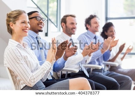 Businesspeople applauding while in a meeting at office - Shutterstock ID 404378377
