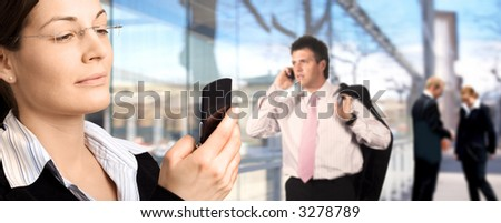 Businesspeople are calling on mobiles in front of a modern office building. - stock photo