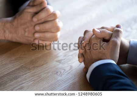 Businesspeople at business meeting making decision thinking unrecognizable businessmen sitting opposite of each other, close up hands clenched resting on desk. Opposition and nervous situation concept