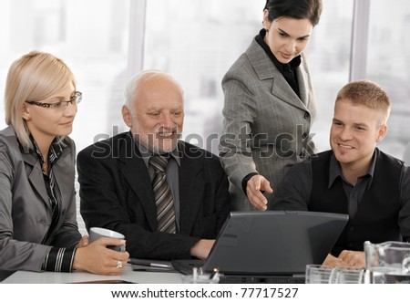 Businesspeople at meeting in office looking at laptop computer, businesswoman pointing at screen, smiling.?