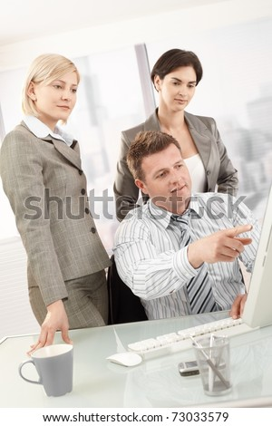 Businesspeople at work, businessman pointing at computer screen, coworkers watching.?