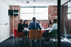 Businesspeople attending their morning briefing in a modern office. Group of creative businesspeople having a discussion during a meeting. Businesspeople working together as a team.