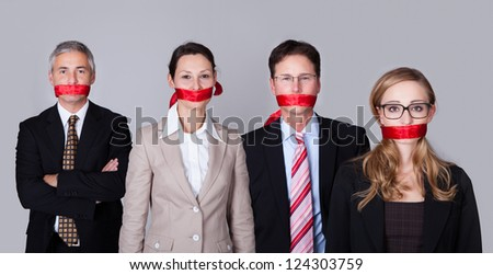 Businesspeople bound by red tape around their mouths standing in a row unable to speak or divulge information