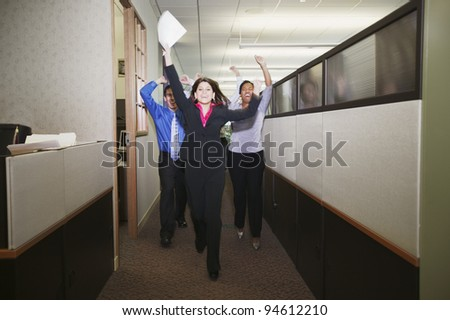 Businesspeople cheering in office - stock photo
