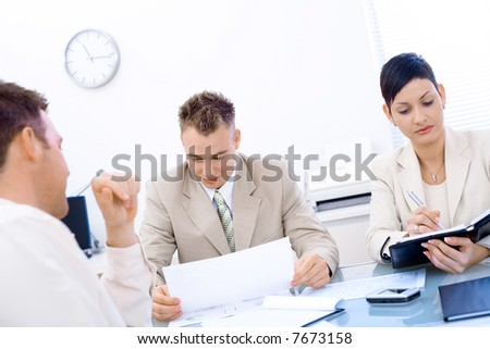 Businesspeople conducting job interview in brightly lit office.