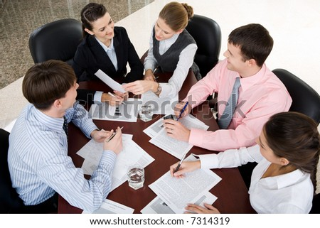 Businesspeople gathered around the table for a meeting, brainstorming - stock photo