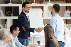 Businesspeople gathered at office meeting middle east appearance and caucasian businessmen shake hands, making agreement closing deal, business partners handshaking after successful group negotiations