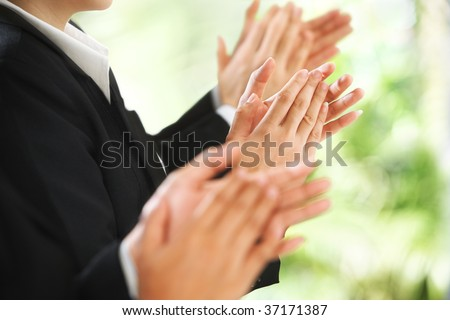 Businesspeople giving applause over the green environment background - stock photo