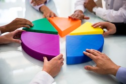 Businesspeople Hand Connecting Multi Colored Pieces Of Pie Chart On Desk