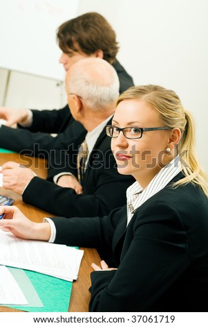 Businesspeople in a team meeting, a woman smiling at the camera