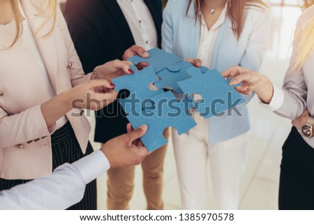 Businesspeople joining puzzle pieces in office Foto stock ©
