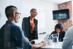 Businesspeople laughing during a briefing in an office. Group of successful businesspeople attending their morning meeting in a modern workplace. Creative businesspeople working together.