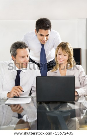 Businesspeople looking at laptop in meeting room.