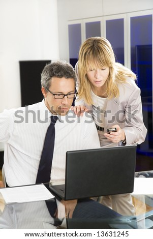 Businesspeople looking at laptop in office. - stock photo
